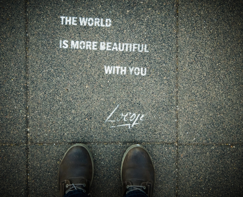 Feet with the world is more beautiful with text on ground